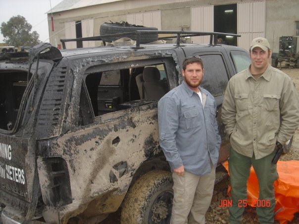 Standing in front of blown up truck